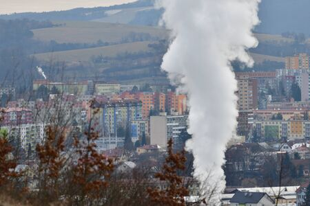 Smoke from the chimney of the thermal power plant rises above the city and pollutes nature