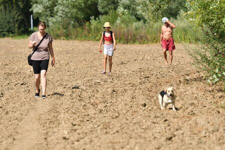Family trip to nature in the hot summer to the river to swim with dog