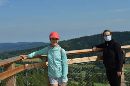 Two girls in a protective mask on their faces on a hike on a tower in nature