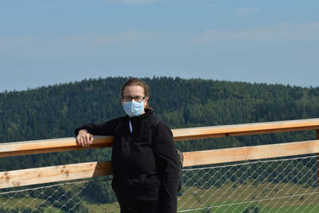 Portrait of a woman's head on a tourist tower in the background with nature and forests