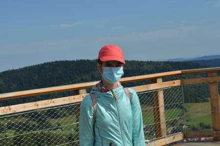 A teenage girl admires the surrounding nature from a tower during a pandemic in a hand on her face