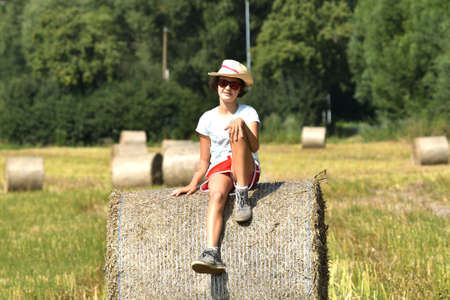 Girl sitting on a meadow after harvest on a stack of straw Imagens