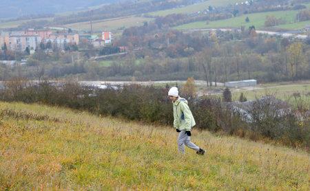 Slim girl runs through a meadow in autumn above the horizon city