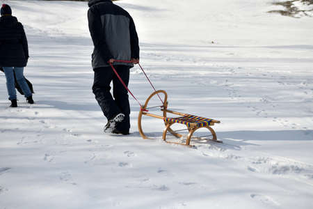 Men and women are pulling sledge up the hill in the winter in the snow 版權商用圖片