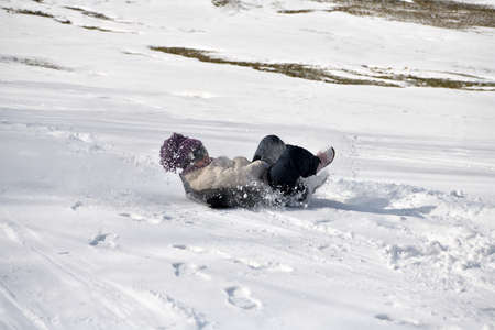 The little boy lies on his back and slides down the slope in the snow