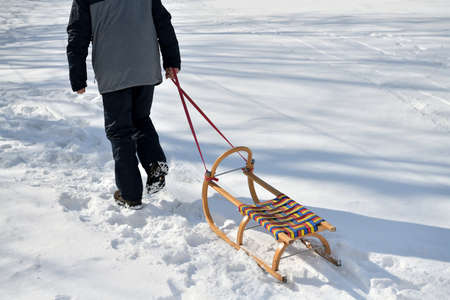 A man pulls a sledge up a hill in the winter tobogganing 版權商用圖片