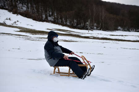 Grandfather slide on the sledge in the winter snow