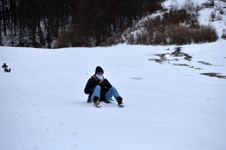 An adult woman sleds down a hill in the winter and brakes with her feet 版權商用圖片
