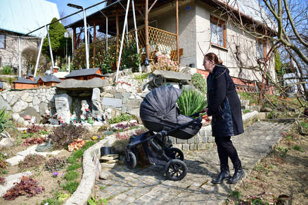 A woman in a black coat walks with a baby buggy carriage around a garden hut 免版税图像