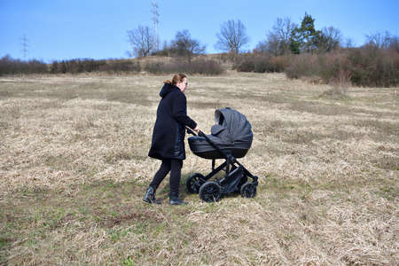 A woman dressed in a black coat on a walk with a baby carriage in the spring nature