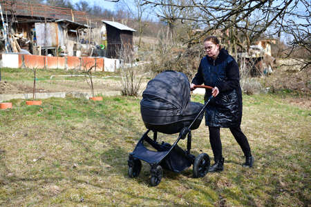 Woman relaxing with a baby stroller around a garden hut in nature