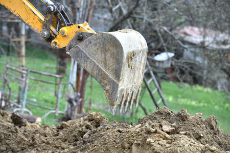 The excavator's shovel picks up the soil while digging on the construction place