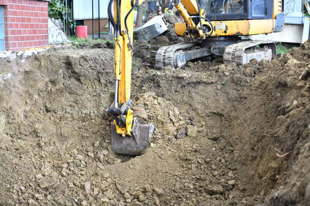 A road excavator digs soil on the foundations of an outbuilding to the house