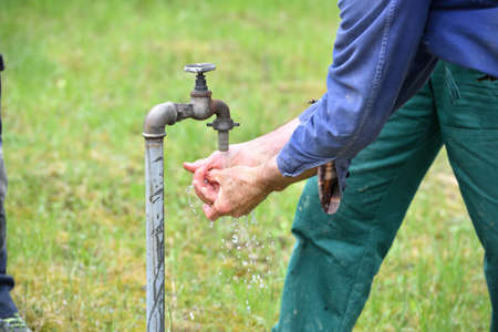 Washing hands on a green meadow from the water supply of a well