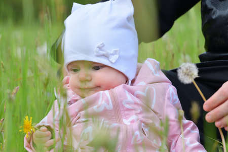 Portrait of infant child sitting in the green grass
