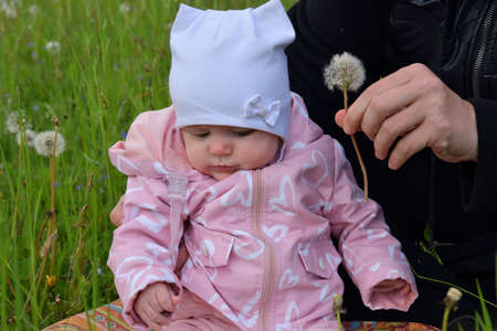 The little infant girl in a white cap and pink clothes is smiling  on green meadow 版權商用圖片