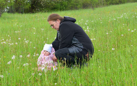 Young mother sitting on a green meadow with a toddler 版權商用圖片
