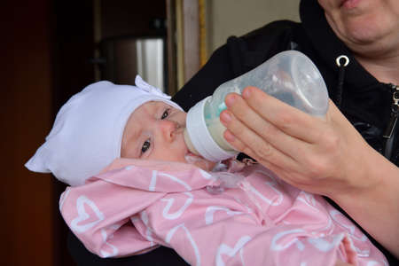 Close relationship of baby and mother during feeding with milk from a bottle