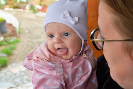 The little infant girl in a white cap and pink clothes is smiling  and is happy