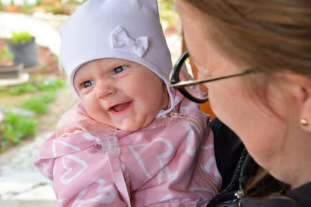 Toddler girl on mother´s hand is smiling and happy