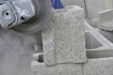 View of a mason's hands on a construction site sawing a block using an electric grinder
