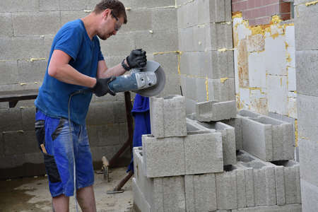 A grinder on a construction site saws bricks using an electric grinder in dust 版權商用圖片