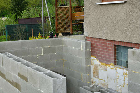 Extension of the walls of prefabricated blocks to the existing cottage 版權商用圖片