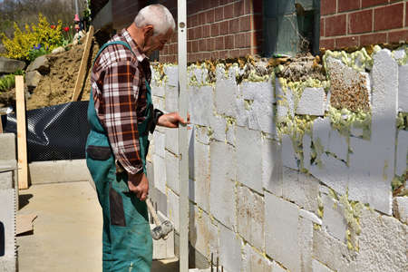The site inspector in green checks the accuracy of the walls using a spirit level