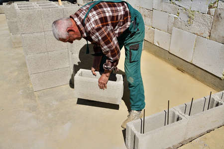 The mason places and prefabricated blocks into the wall at home on the construction site
