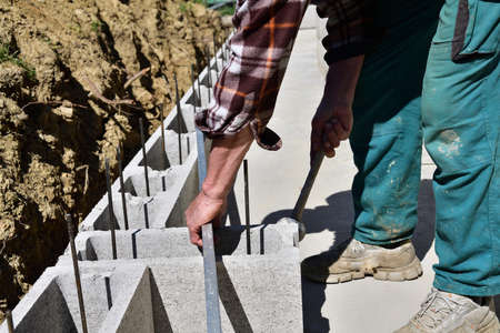 The mason on the construction site measures the perpendicularity of the walls with a spirit level