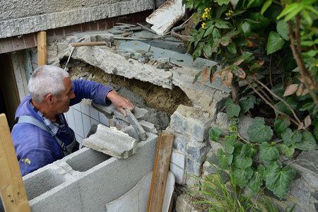 The mason checks the accuracy of the walls using a spirit level Stock Photo