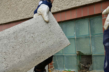The mason puts prefabricated blocks from concrete on the wall