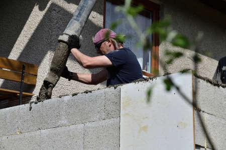 A concrete worker on a construction site concretes walls using a machine