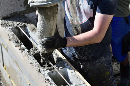 Detail of a concrete pump from which concrete is poured into walls on the construction site