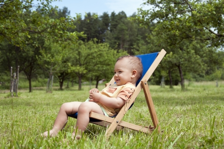 Baby or a toddler child relaxing on a sunbed or a deck chair in a garden  photo