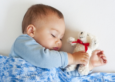 Portrait of a little baby boy sleeping under a blue blanket holding a white teddy bear soft toy