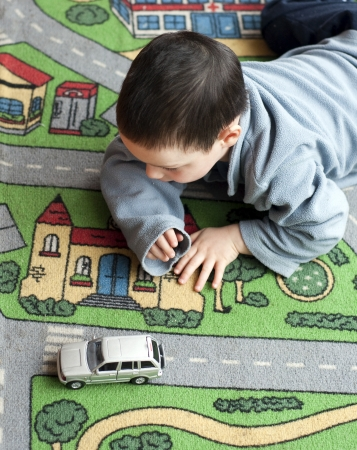Small child boy playing on a road themed carpet with a toy car.
