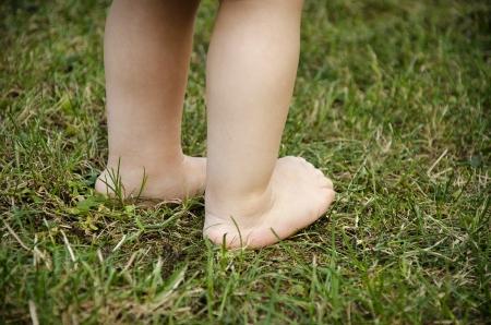 pie bebe: Pequeños pies del bebé del niño de pie sobre una hierba verde. Foto de archivo