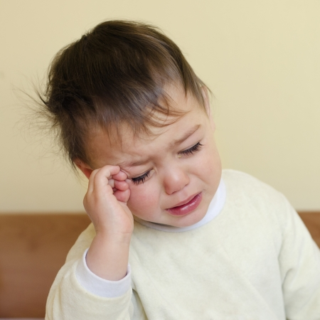 face of infant: Sleepy toodler child crying in a bed after waking up or before giong to sleep