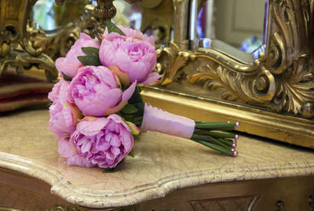 bridal bouquet: Wedding bouquet of pink peony flowers on antique dressing table with mirror