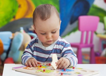 jardin infantil: Peque�o ni�o o una ni�a beb� que juega con las formas del rompecabezas en una mesa baja en una colorida sala de ni�os en una guarder�a o al preescolar Foto de archivo