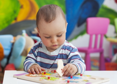 playgroup: Small toddler or a baby child playing with puzzle shapes on a low table in a colorful children room in a nursery or preschool