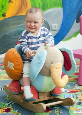children playing with toys: Happy child - small toddler or a baby - playing in a children room, rocking on a toy elephant.