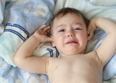 Baby or todler crying in the bed.   photo