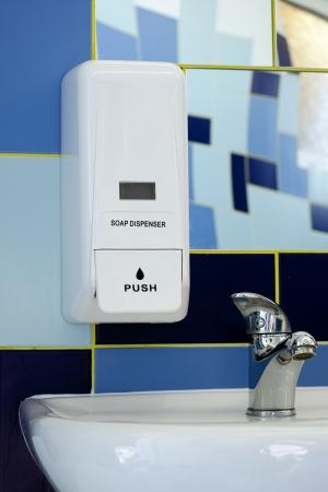 Soap dispenser above the sink or basin in blue tile bathroom.  photo