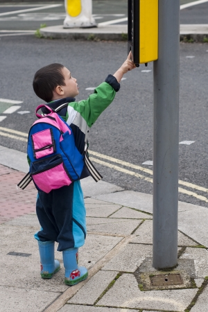 A child boy standing on a pavement or a side walk pushing the button on the traffic signals for pedestrian crossing, road safety concept. Stock Photo