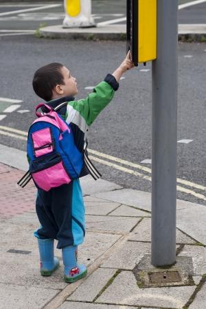 niño empujando: Un muchacho de niño de pie en una acera o un paseo lateral pulsando el botón de la señal de tráfico de paso de peatones, el concepto de la seguridad vial.