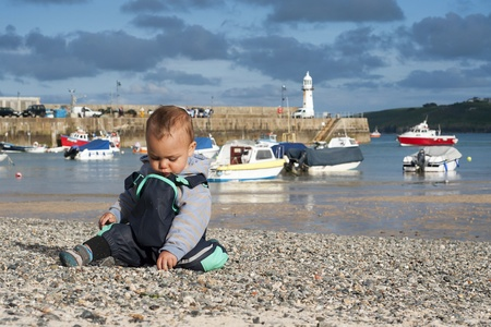 Pebble Beach: Toddler child, boy, on pebble seaside beach in the village port or harbour; boats and peer in the view; St. Ives, Cornwall, England, UK.