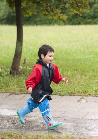 Small boy running through a puddle on the path in a park after a rain  photo