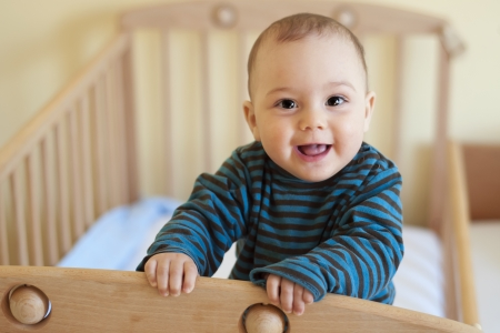 Baby with a cute happy face standing in a cot. Stock Photo